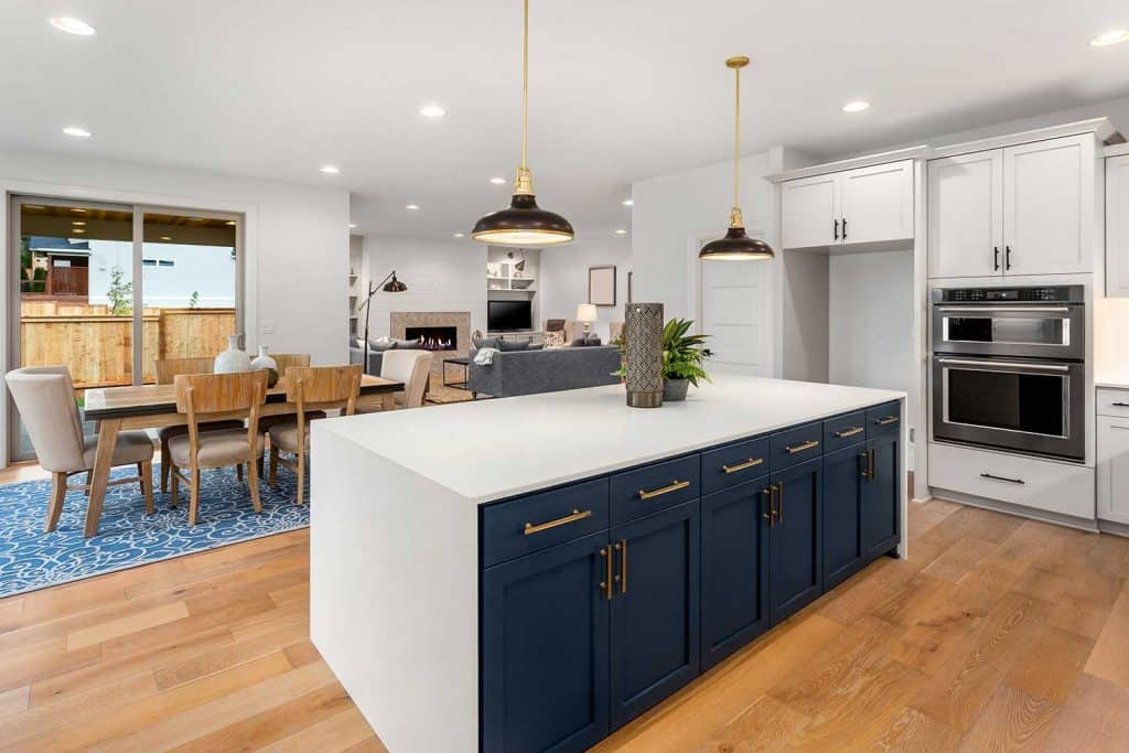 Beautiful kitchen in new luxury home with large island, pendant lights, and hardwood floors