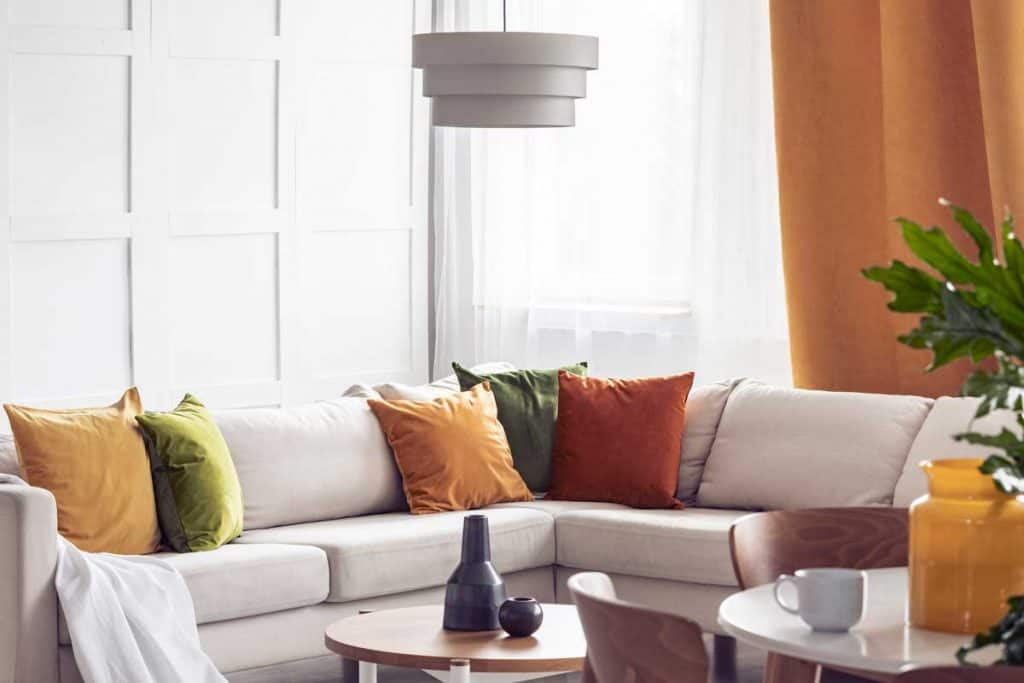Lamp above table in bright living room interior with yellow pillows on white corner sofa