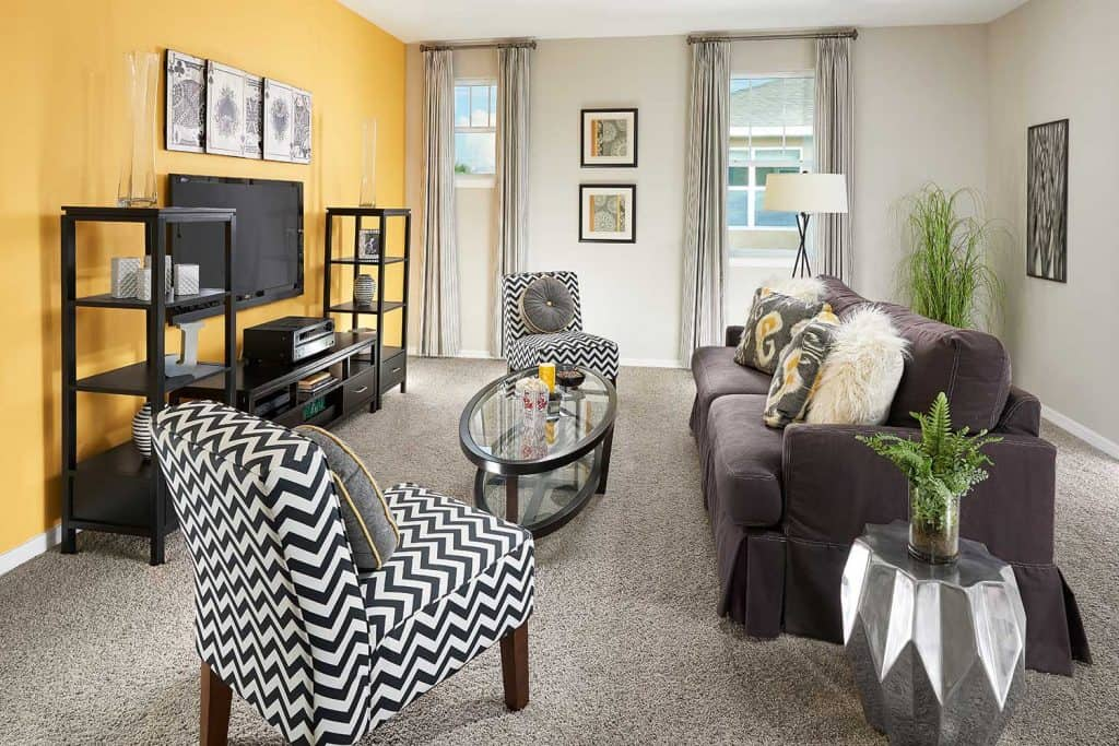 Living room with yellow accent wall, flat screen tv, couch and a carpet floor
