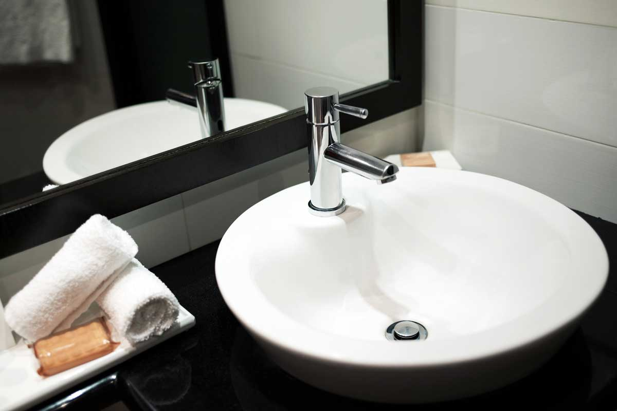 Modern bathroom sink with mirror reflection - with towels top view, How Far Should A Faucet Extend Into The Bathroom Sink?