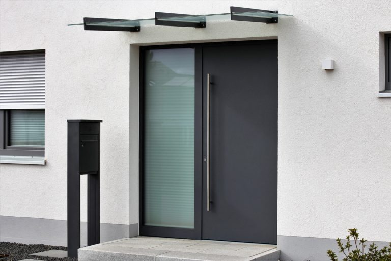 A modern contemporary house with a steel door and a glass steel framed awning, What Is The Safest Front Door? Here's the Answer