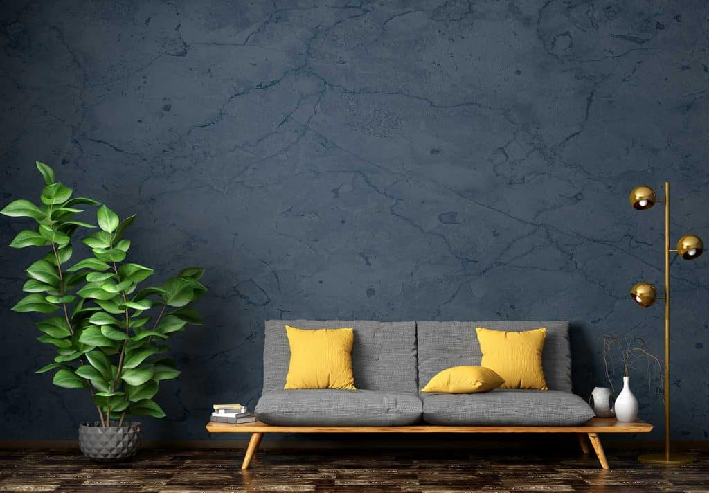 Modern interior of living room with gray sofa, home plant and floor lamp against blue stucco wall