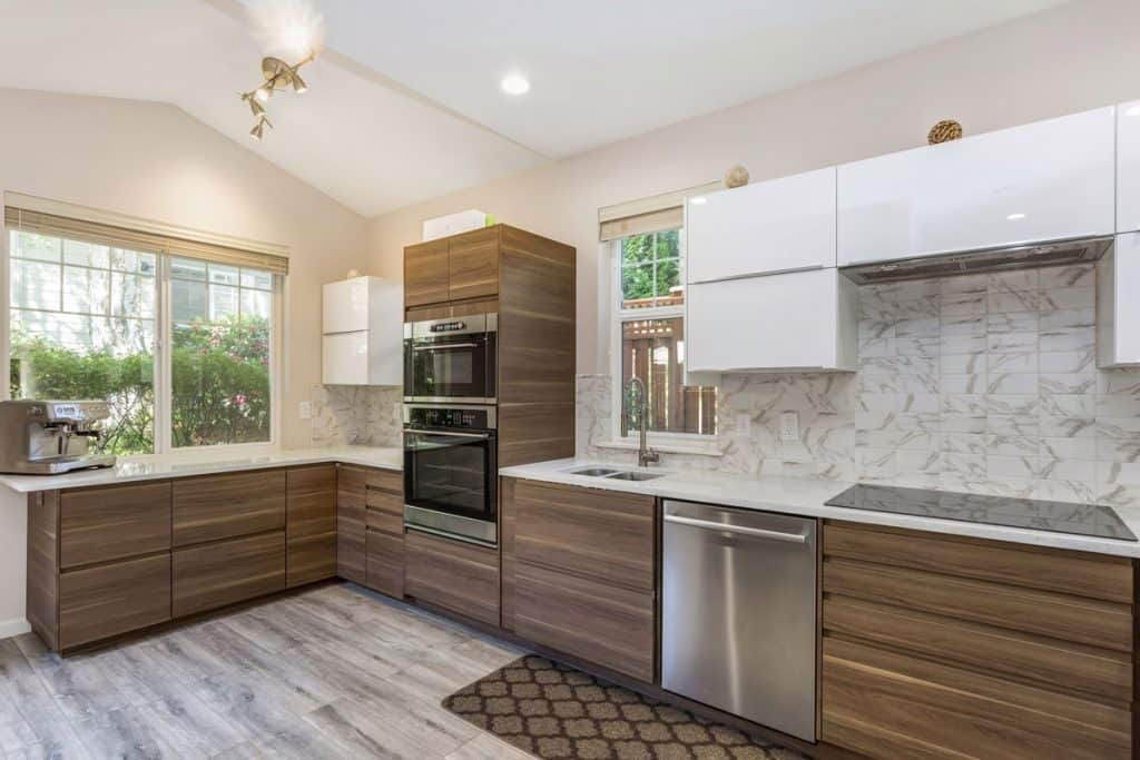 Modern kitchen with wooden laminated panels and a white countertop with hanging white paneled cabinets