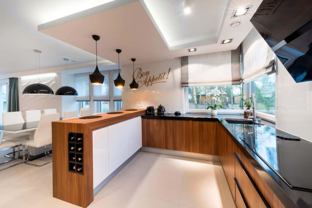 Modern luxurious kitchen with wooden cabinets, black hanging lamps, black granite countertops, and a white tiled flooring