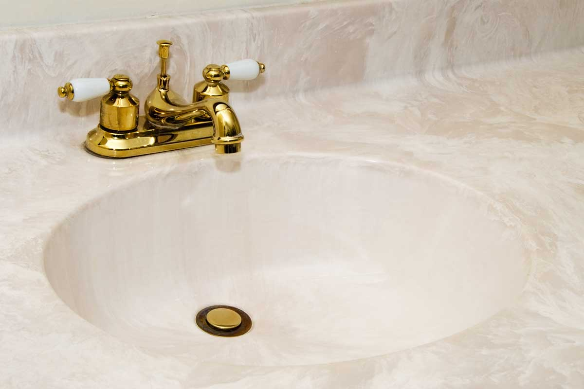 New cultured marble bathroom sink with gold finish faucet and copy space