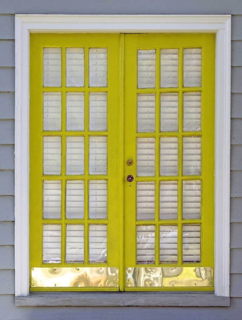 Newly yellow painted exterior double French doors with shiny metal base plate