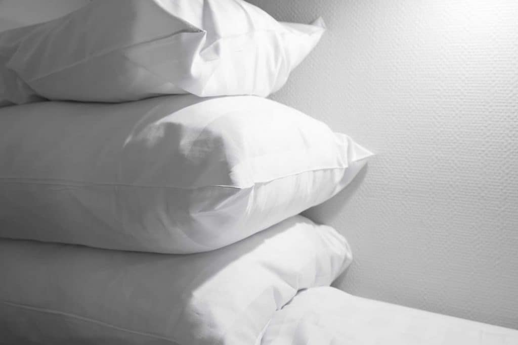 Pile of white pillows lying on empty bed