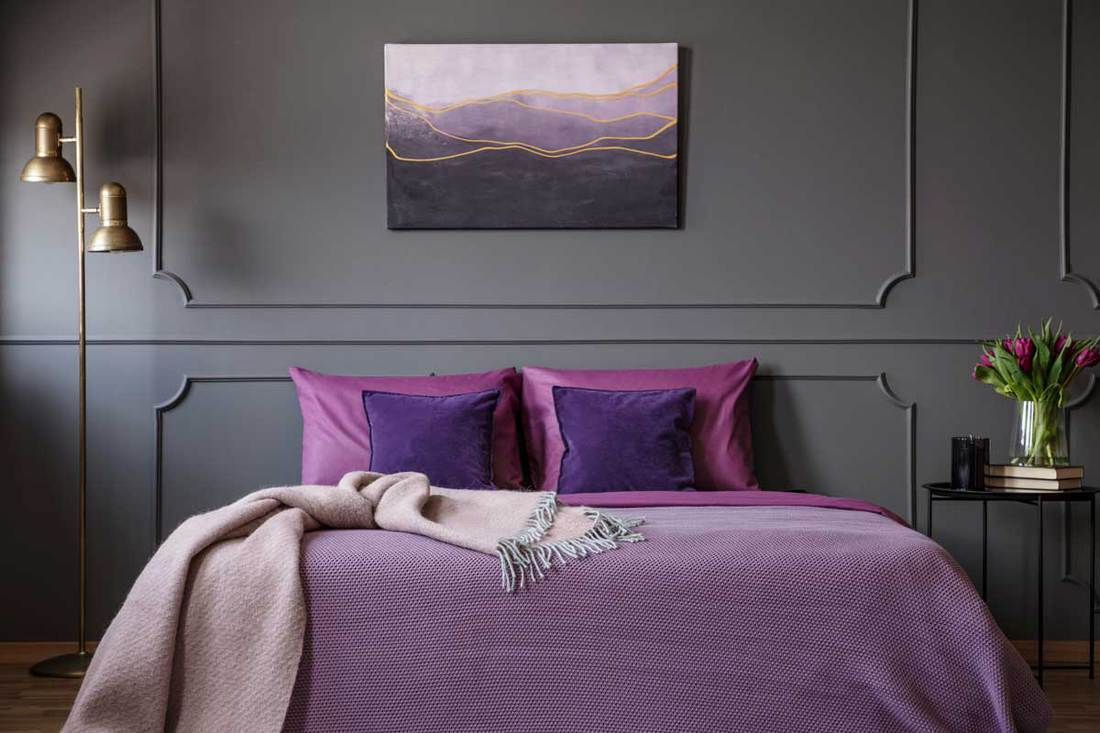 Pink blanket on violet bed in elegant bedroom interior with painting on grey molding wall