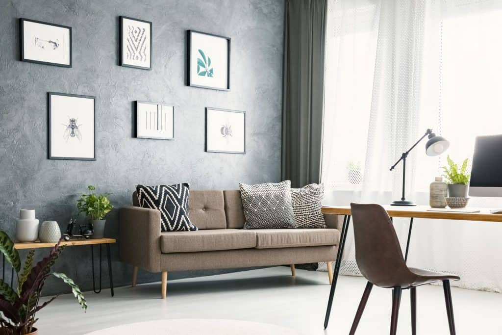 Bright home office interior with a sofa, graphics, desk with a computer, lamp and modern clock
