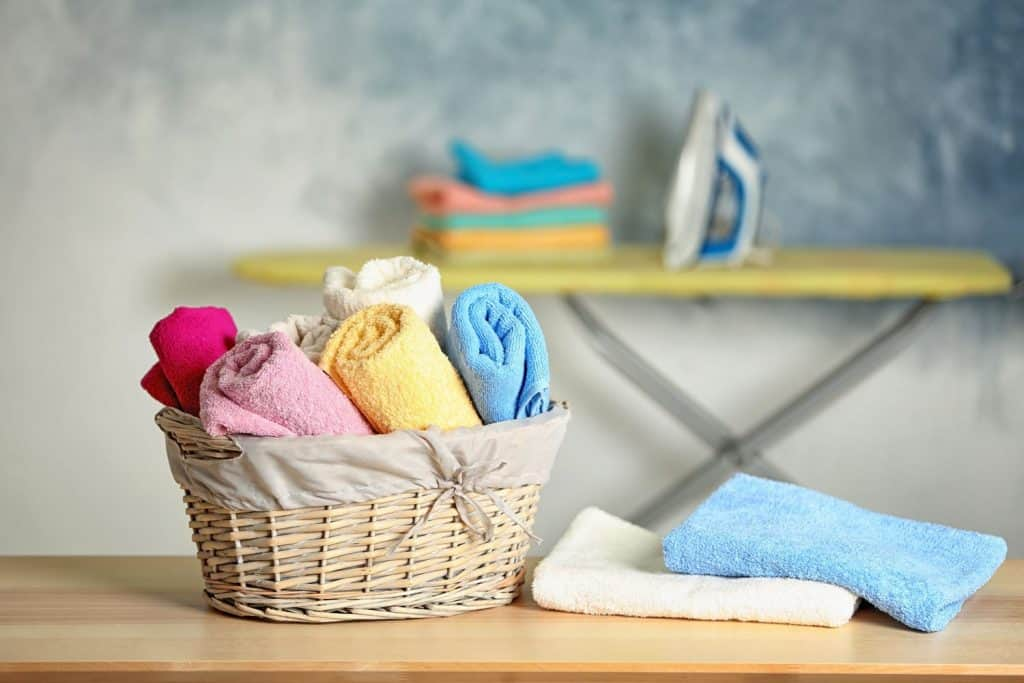 Rolled bath towels placed inside a small basket