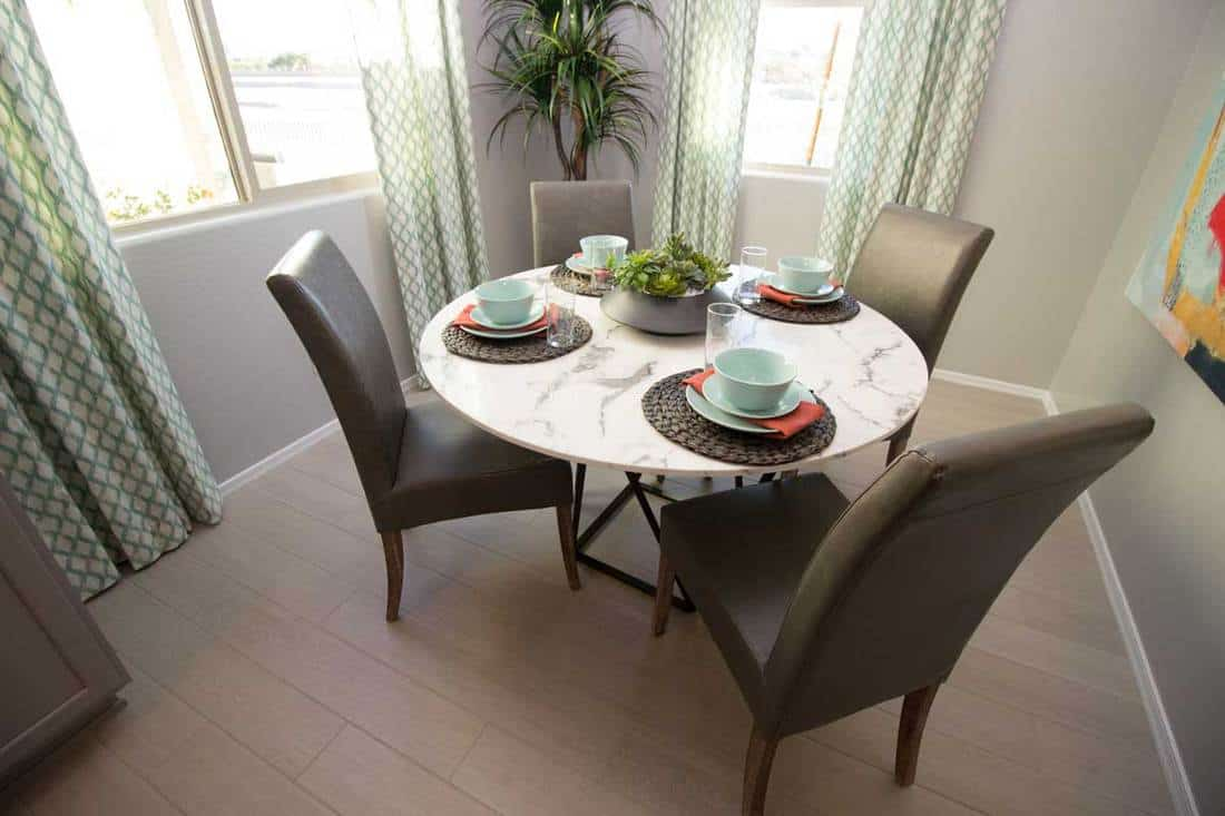 Round Marble Table With High Back Chairs And Place Settings in square room
