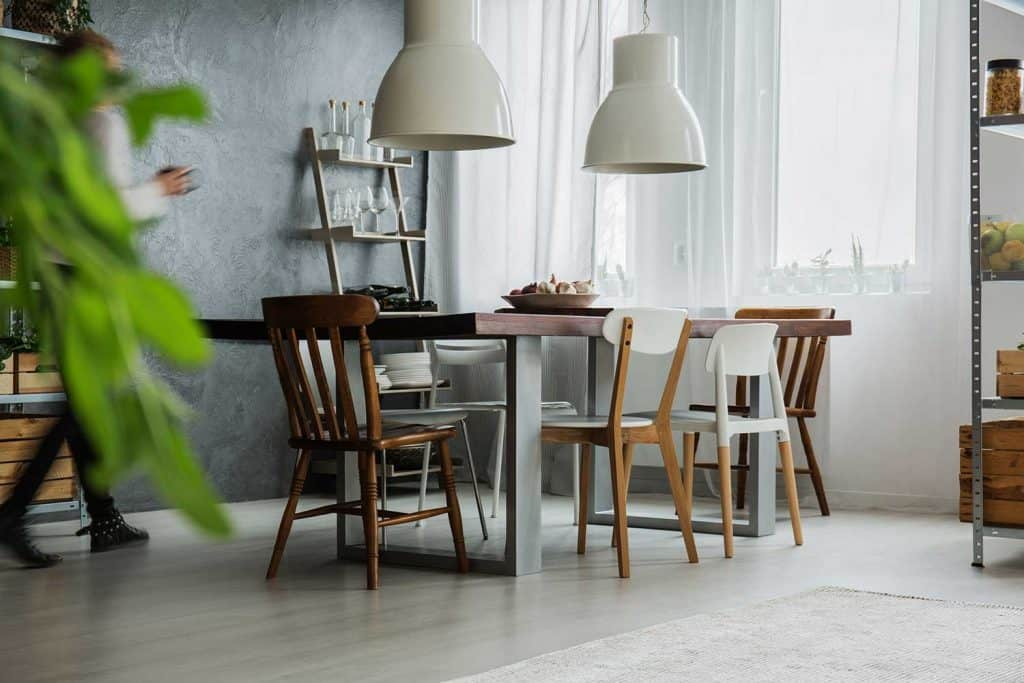 Rustic table, different chairs and dark wall in dining room