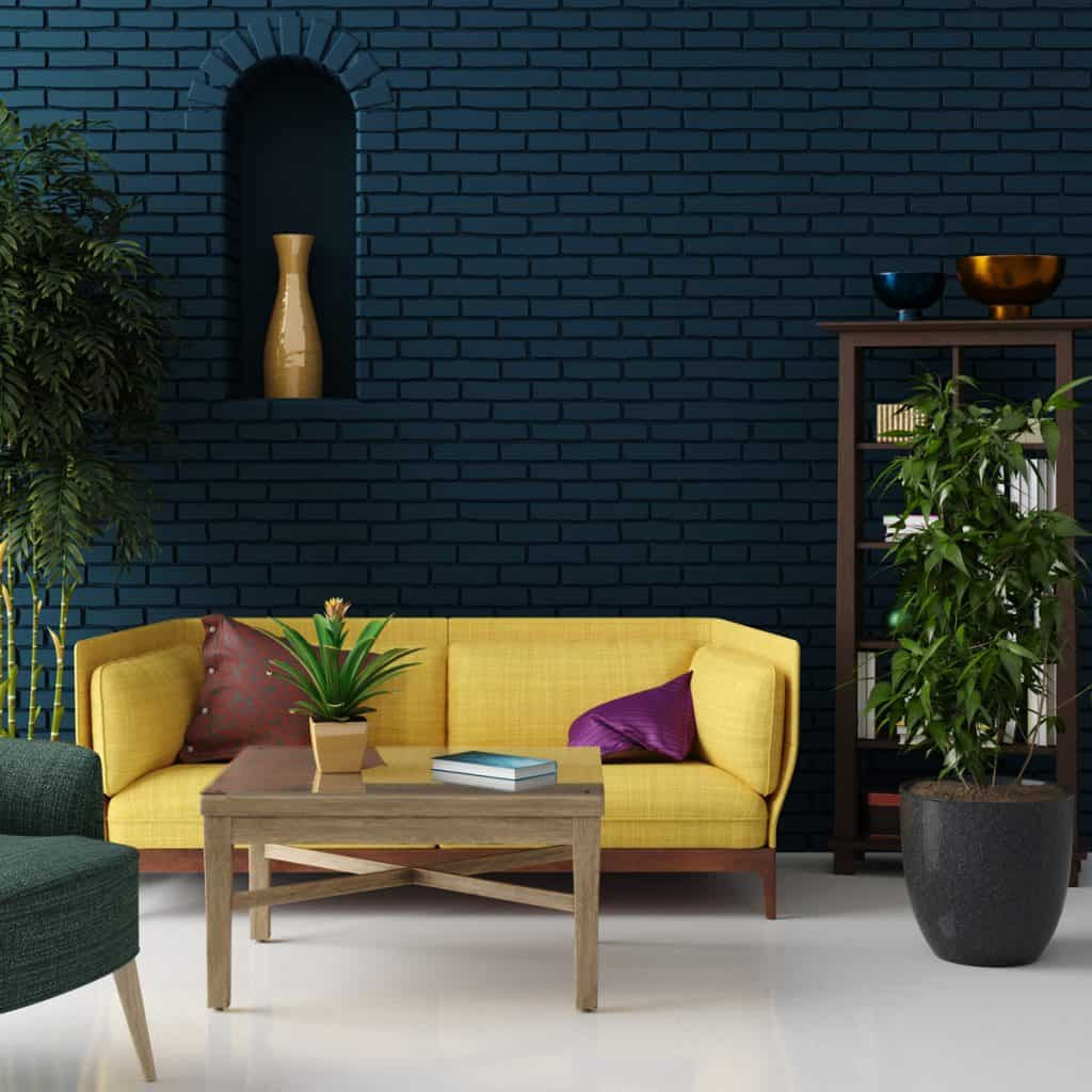 Scandinavian themed living room with a yellow couch and a blue brick wall on the background