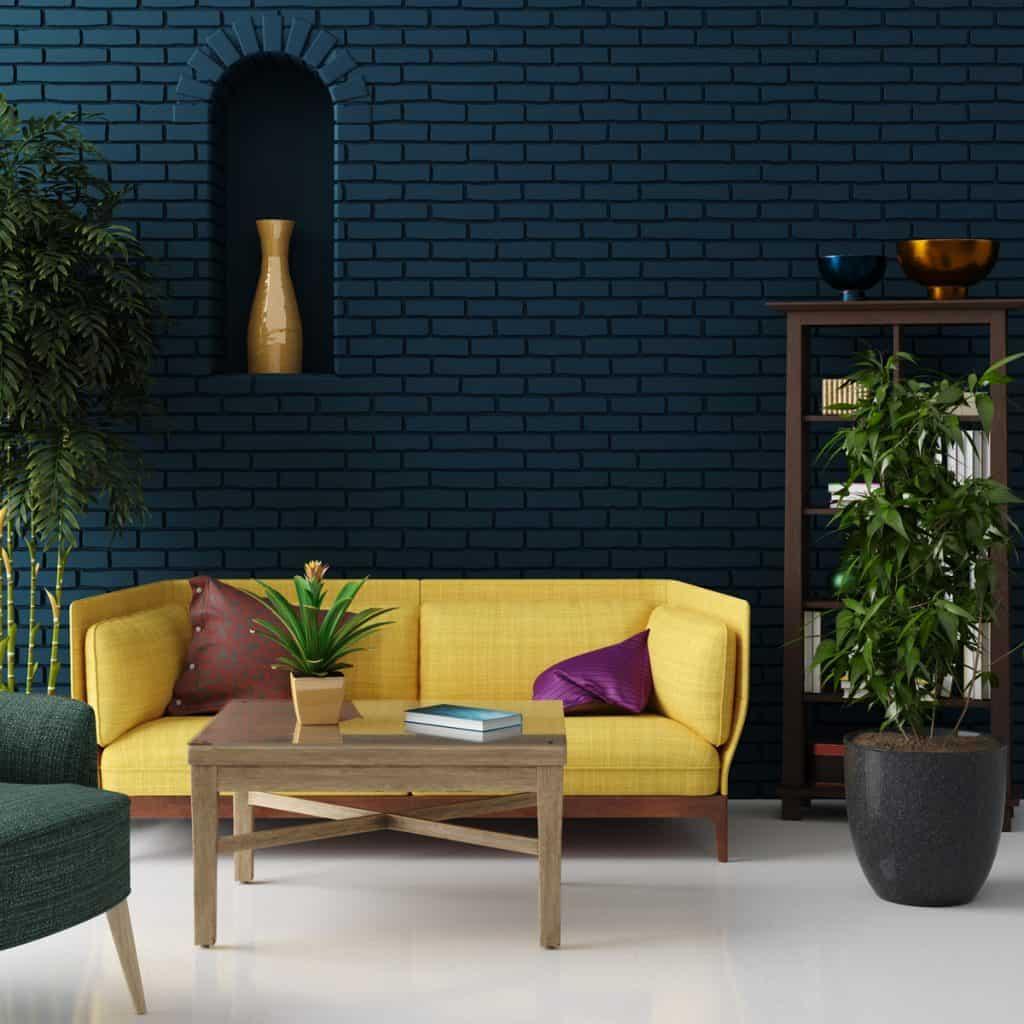 Sarı bir kanepe ve arka planda mavi tuğla duvar bulunan İskandinav temalı oturma odası