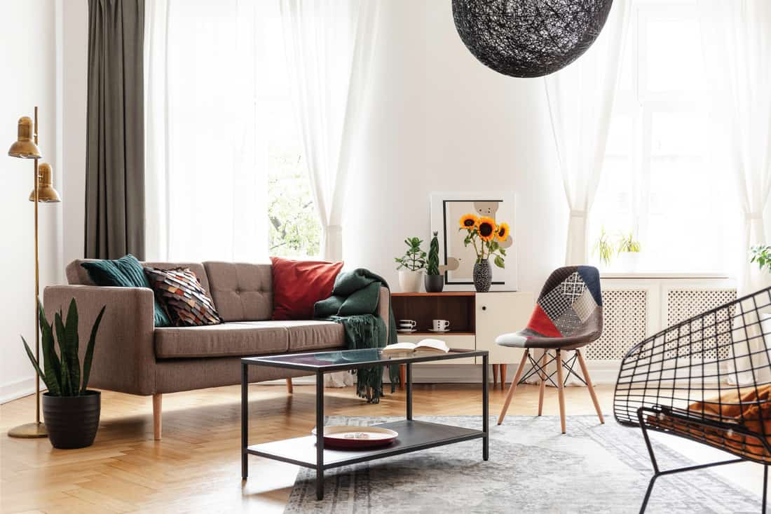 Simple brown sofa with cushions in an eclectic white living room interior with natural light coming through big windows