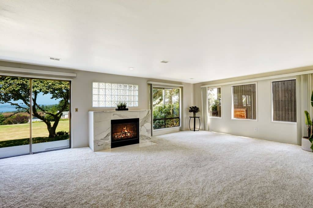 Spacious white themed living room with carpet covered floor and a fireplace with white tiled mantel