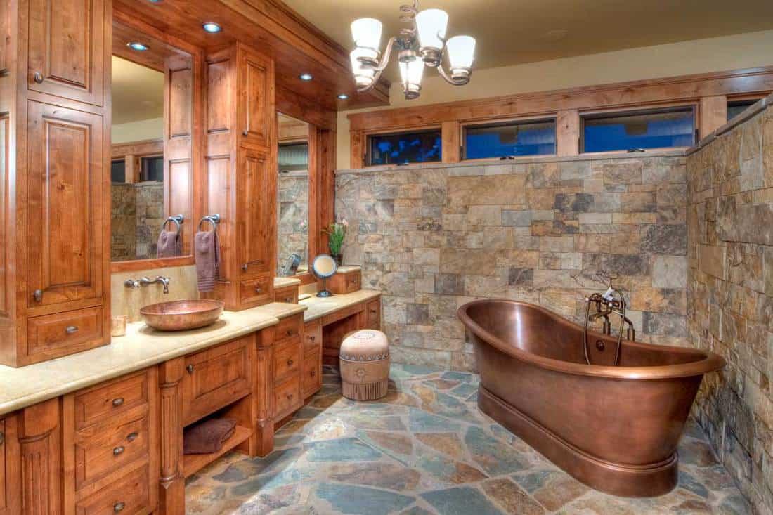 This elegant bathroom has a copper bathtub, and a copper sink