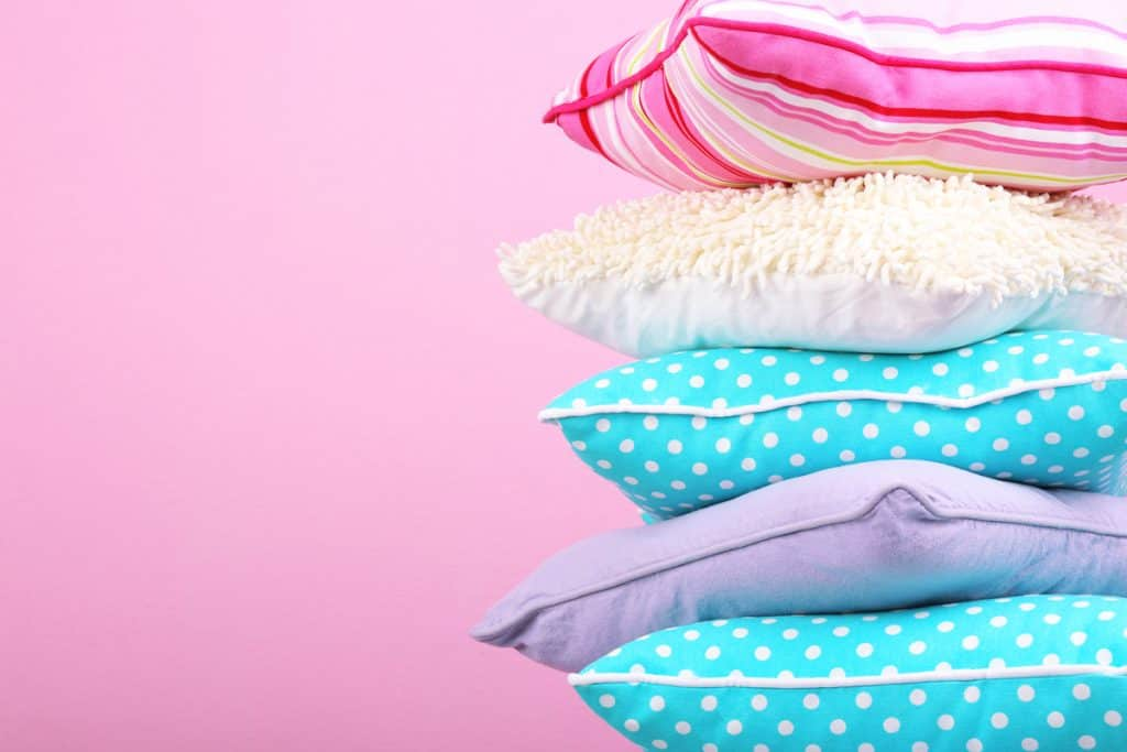 Five different colored pillows on a pink background