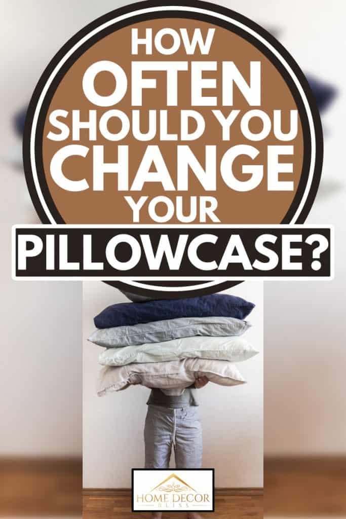 Man holds large pillows of various colors, How Often Should You Change Your Pillowcase?