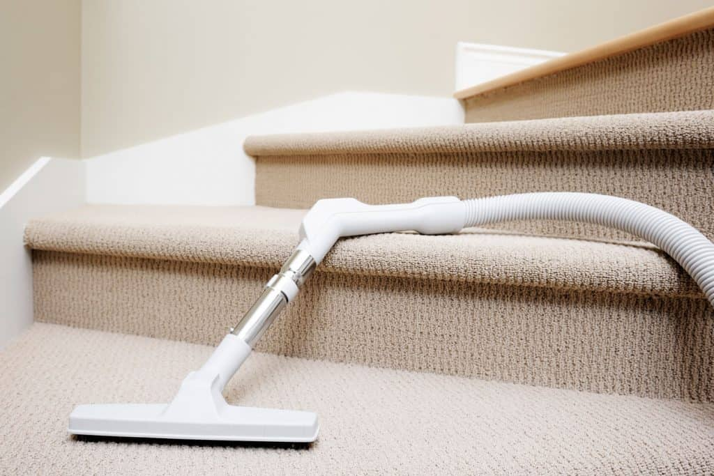 Vacuum cleaner lying down in stairway covered by carpet, domestic