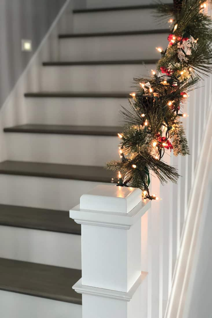 White staircase with holiday decorations and Christmas lights and a fire place in the background
