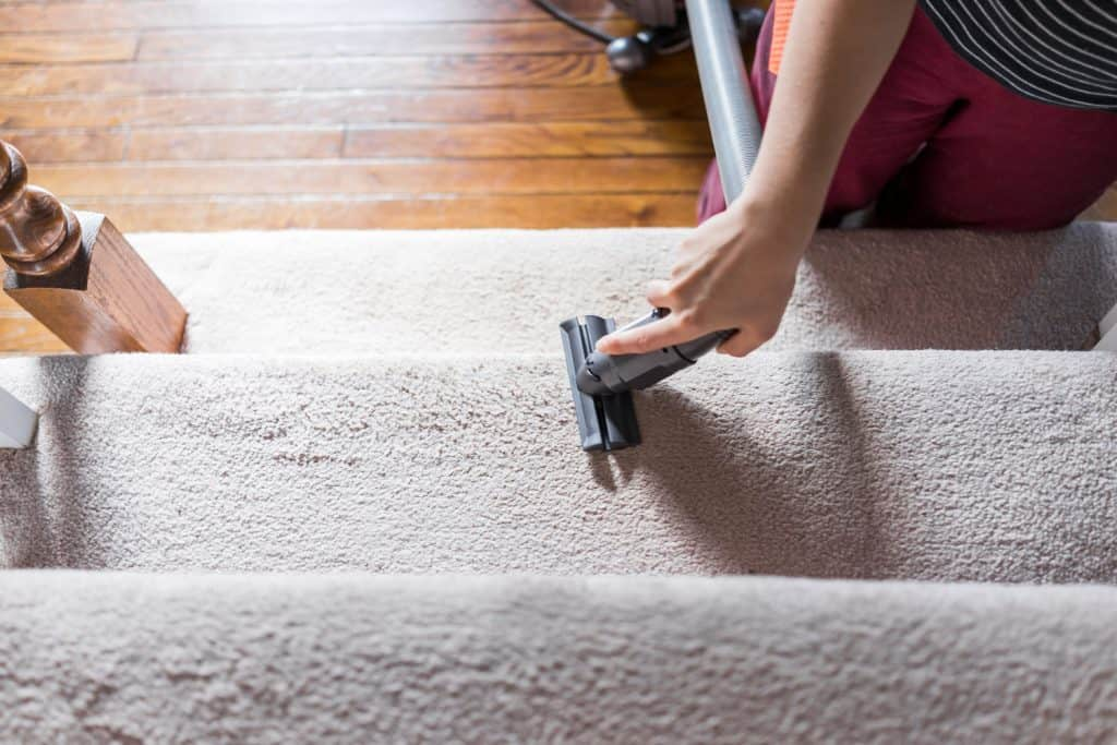 Young woman hand closeup flat top view looking down vacuuming using vacuum on carpet floor inside interior of house living room stairs, steps or staircase, domestic life