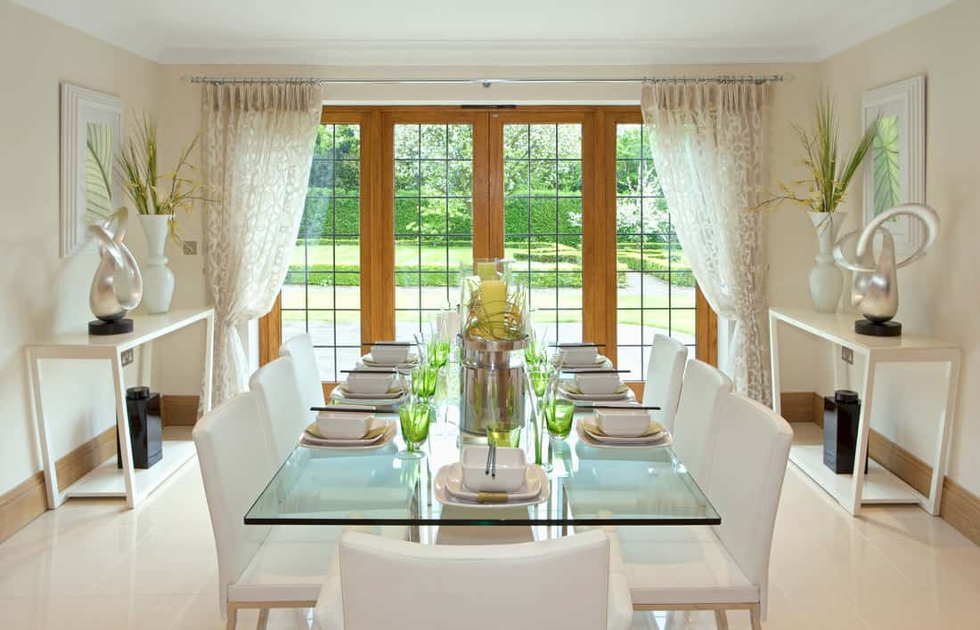 a light and airy dining room with a lovely garden view in a luxury expensive new home with wooden french doors