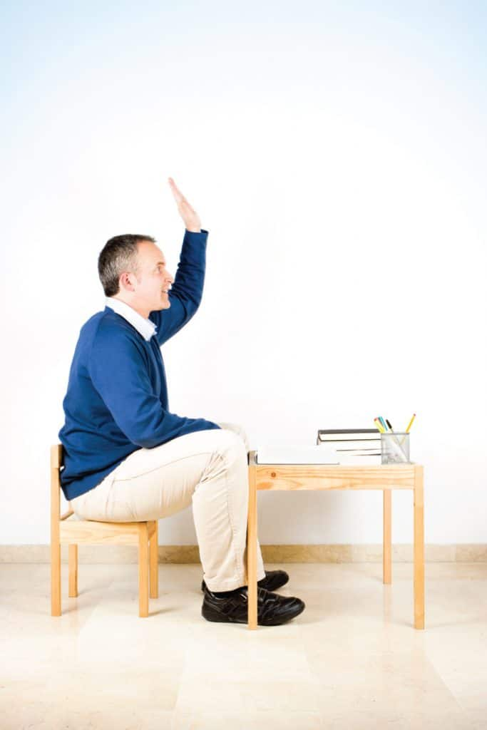 Adult man sitting on a low chair with low desk