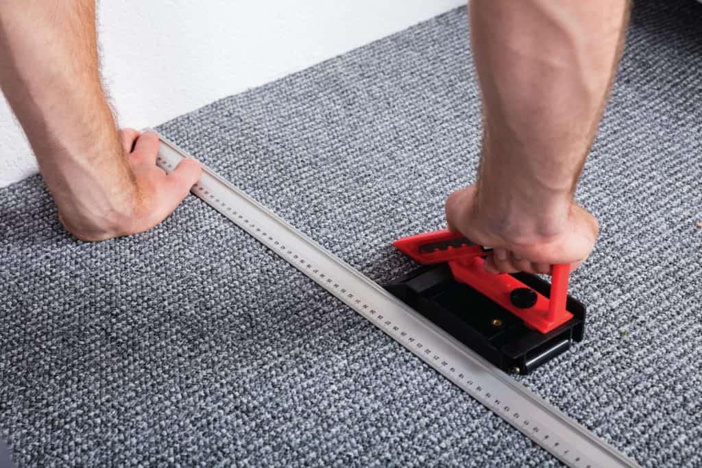 Man laying gray carpet on the floor