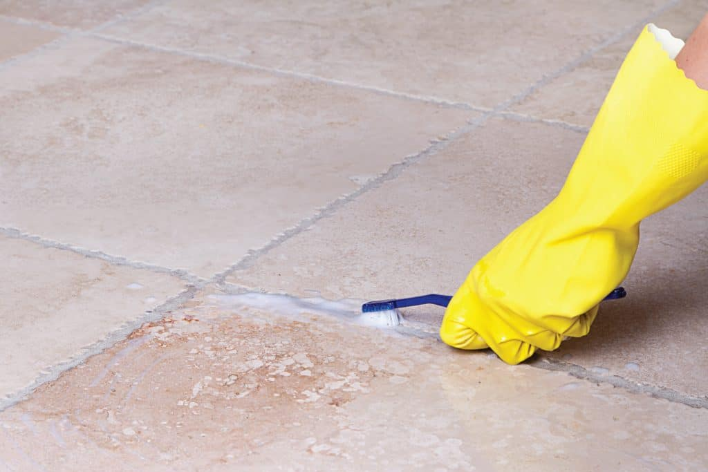 hands with yellow rubber gloves cleaning tile grout with toothbrush
