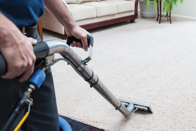 Man holding a high performance vacuum machine cleaning a carpet, Do You Tip Carpet Installers And Cleaners?