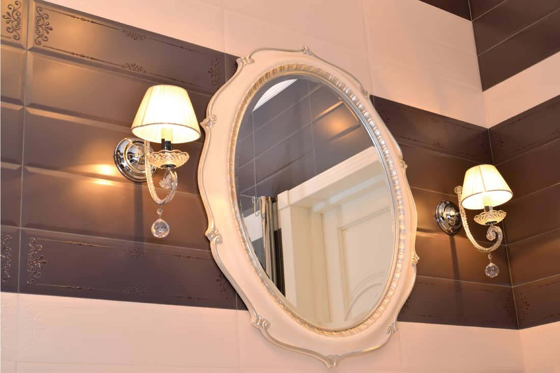 modern classic bathroom with 2 sconces and a vanity mirror