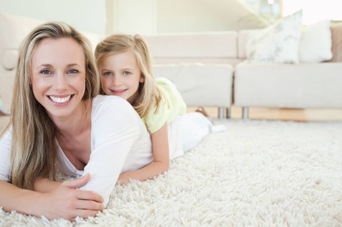 mother and daughter lying down on a high pile floor carpet