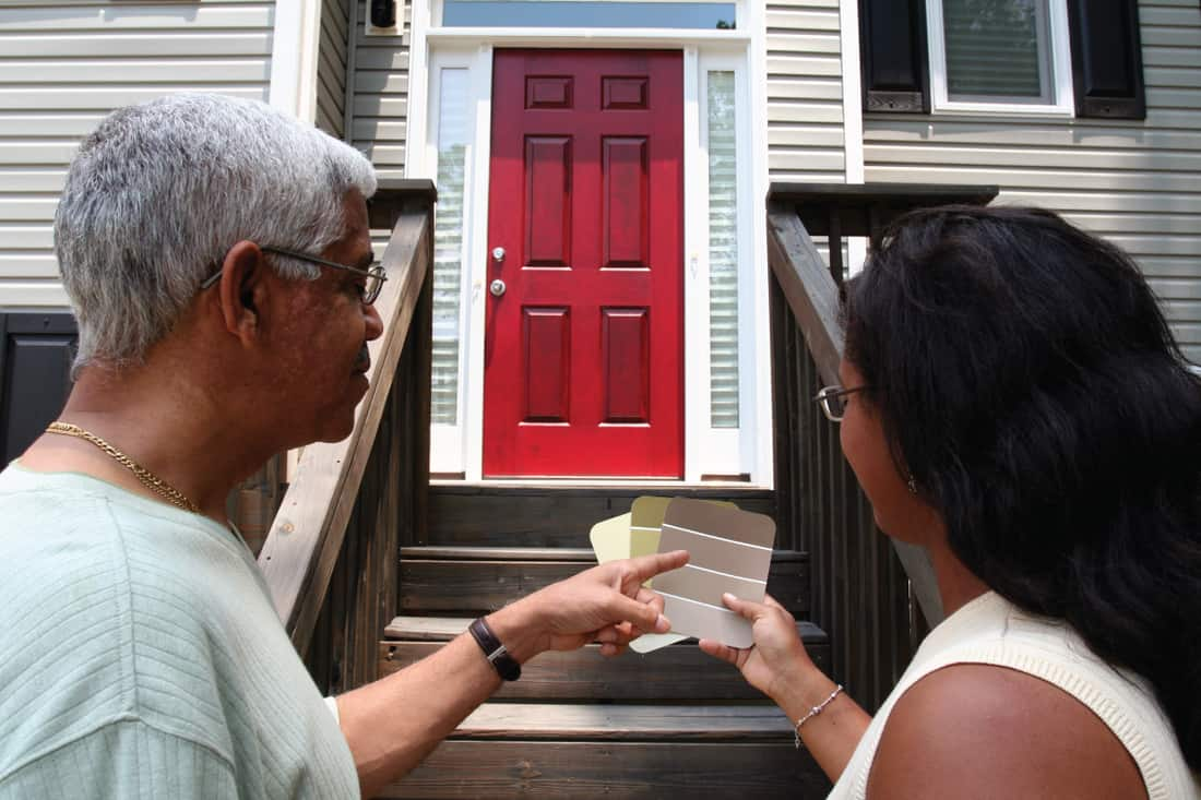 Two women picking a color before painting their currently red front door