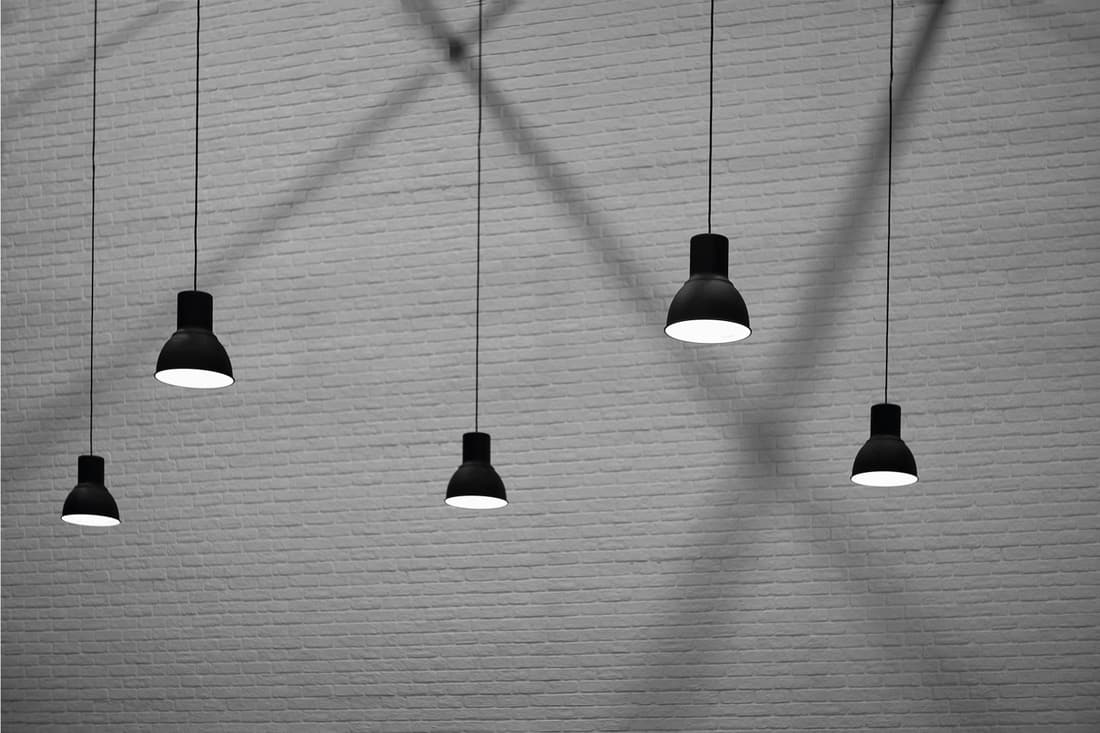 5 hanging pendant lamps with light and shadow on surface of brick wall