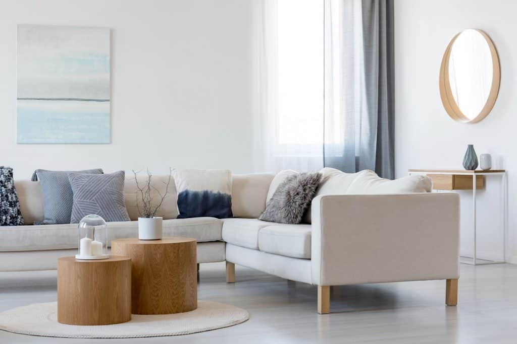 A Scandinavian themed living room with a white sectional couch, a round coffee table, and a white round carpet