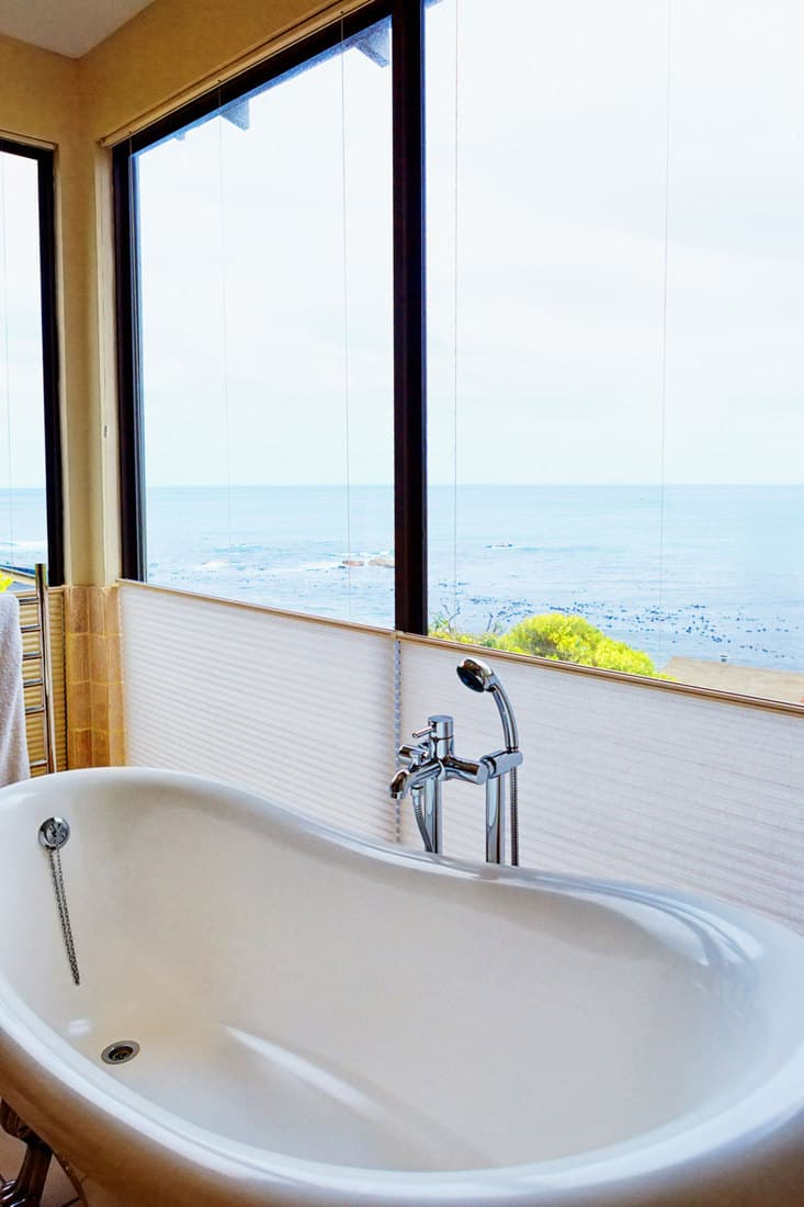 A bath in a luxury hotel is situated next to a window with a view right over the Atlantic Ocean