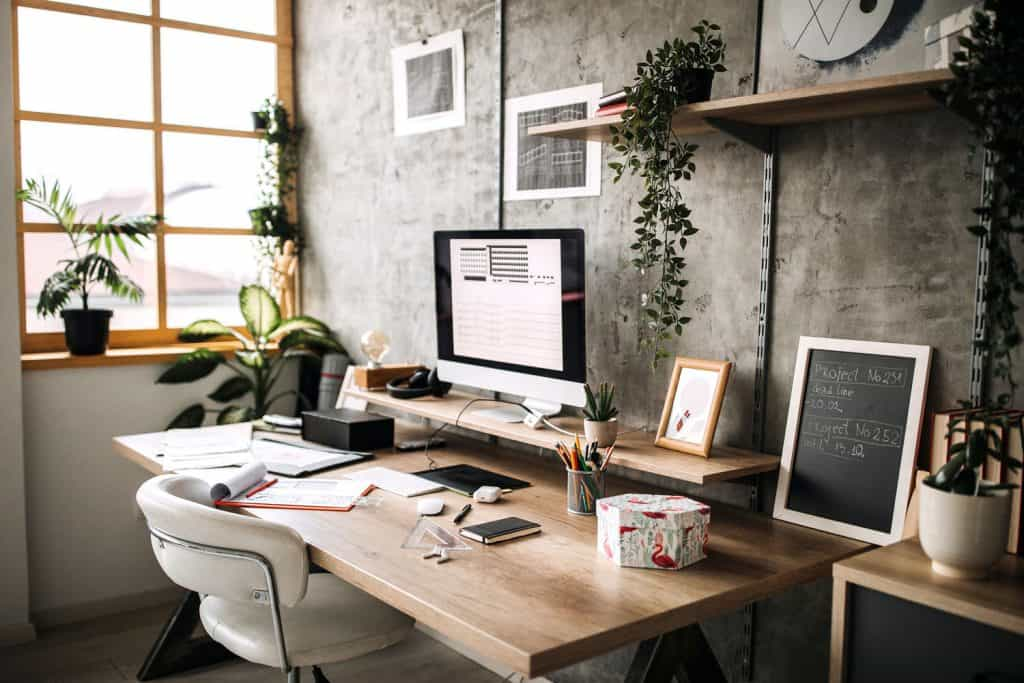 A beautiful home office with a wooden desk and white round chair matched with indoor plants