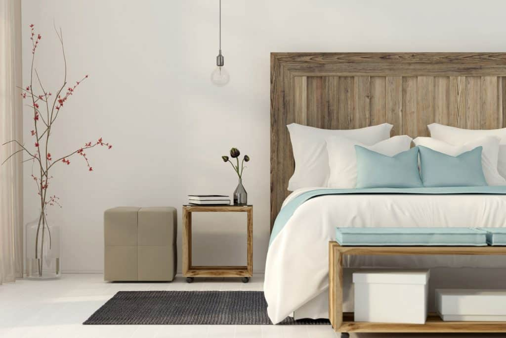 A bedroom with cream painted walls, a wooden header and teal colored beddings