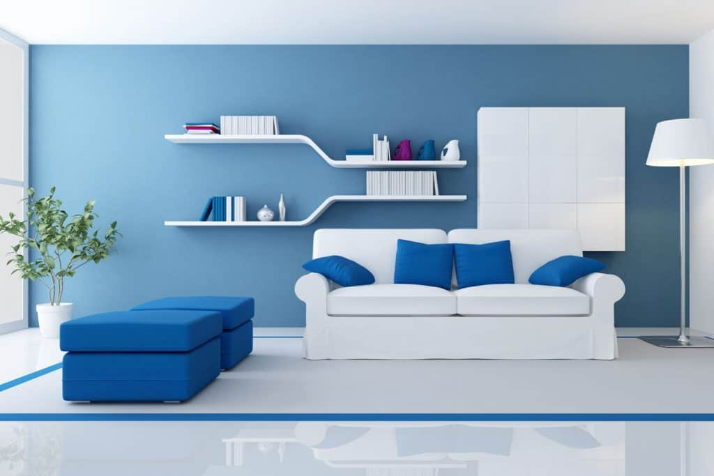 A blue contemporary living room with a white sofa, blue ottomans and a blue accent wall with dividers