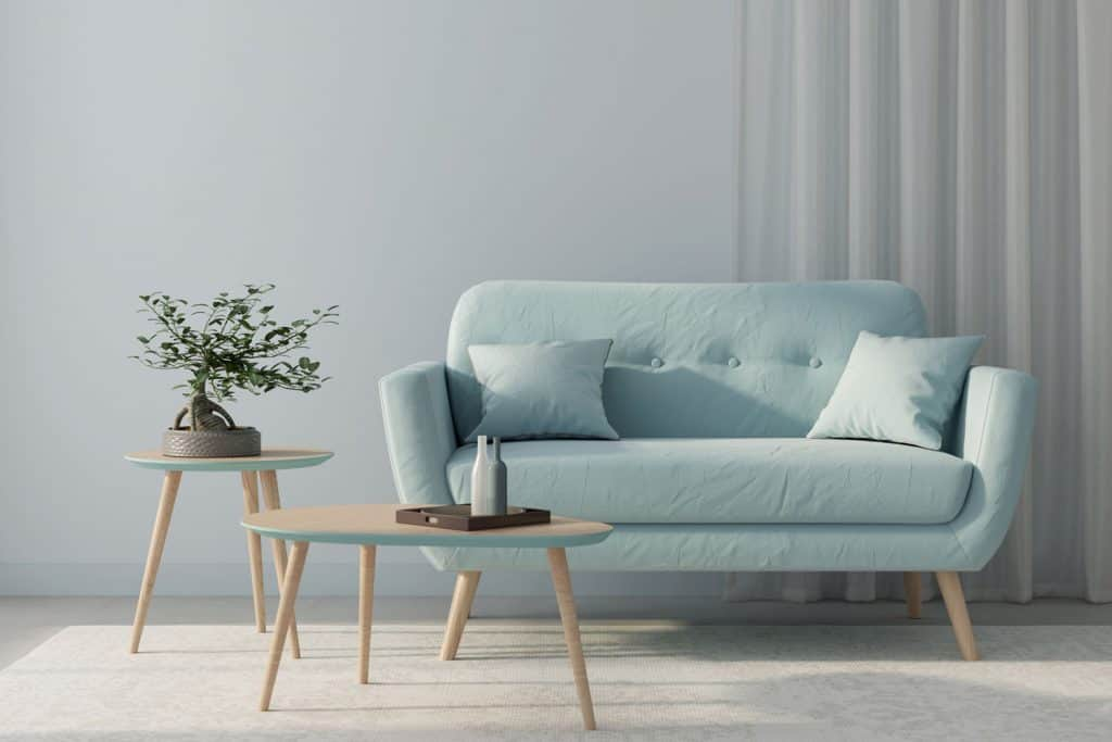 A blue sofa, round wooden table, and a carpet on the flooring inside a blue walled living room