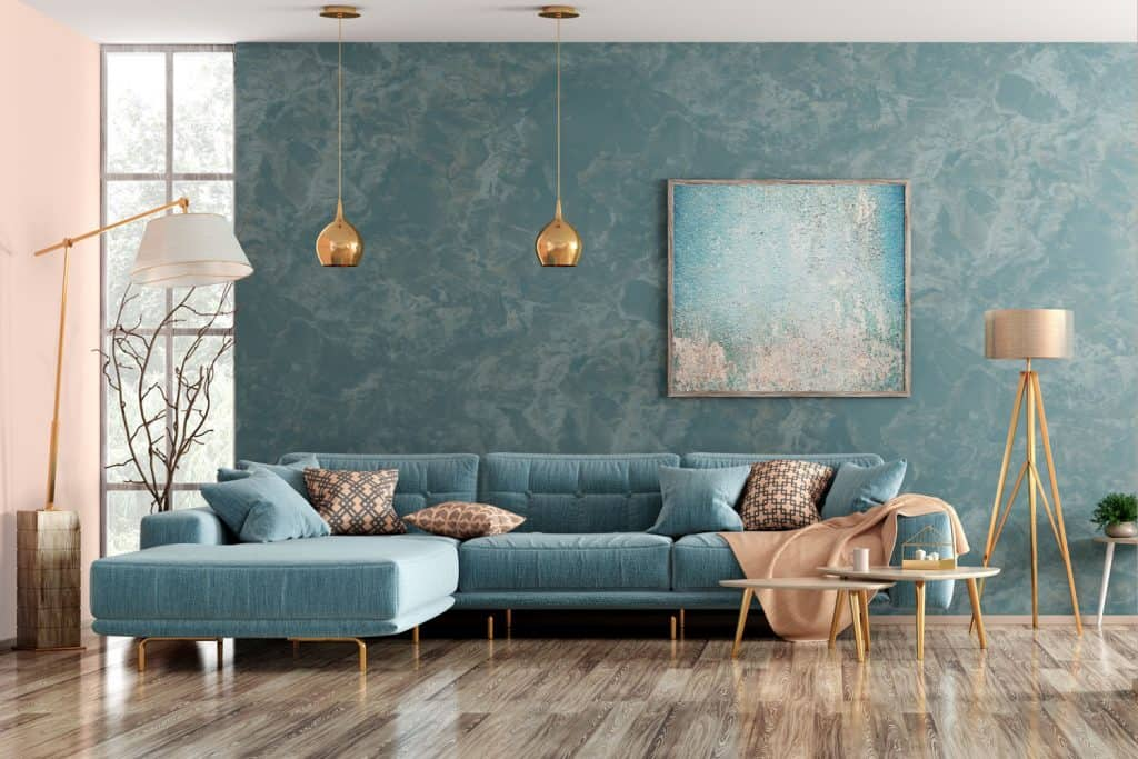 A Bohemian themed living room with a blue accent wall, blue sectional couch, wooden laminated flooring, and two golden hanging lamps