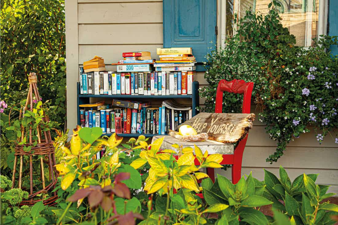 A bookshelf full of books of different genre is placed on the porch of an old house