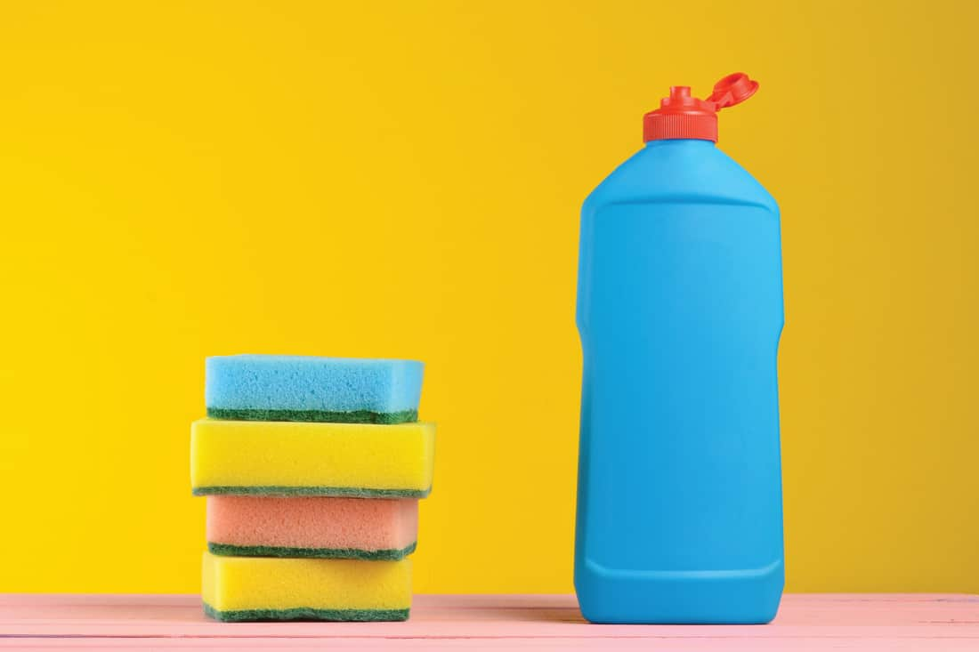 A bottle of dishwashing liquid and sponges on a wooden pastel color table against a yellow wall background
