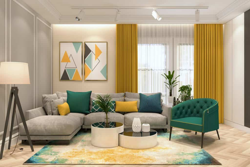 A bright living room with mustard yellow colored curtains, dark green colored chair and gray colored couch