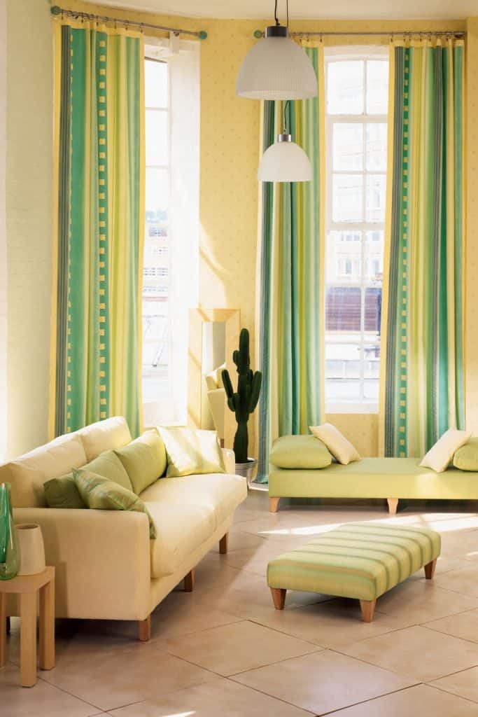 A bright colored living room with bright green colored curtains and a cream colored couches with green throw pillows