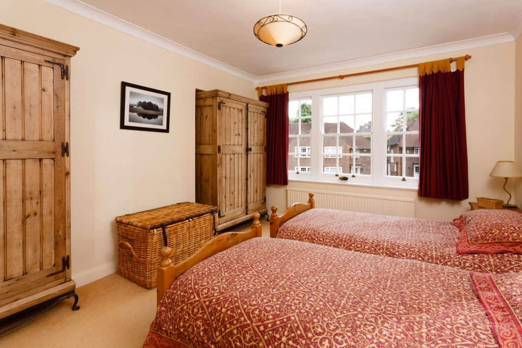 A classic rustic bedroom with red floral beddings, wooden cabinets and cream painted walls