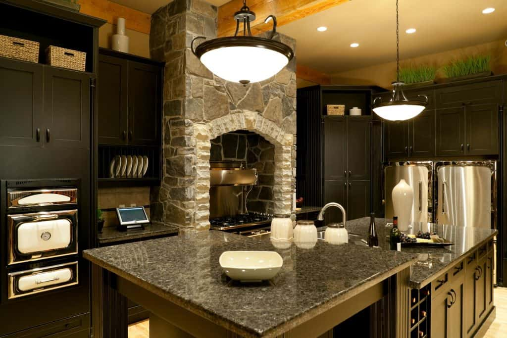 A classic themed kitchen area with black marble countertop
