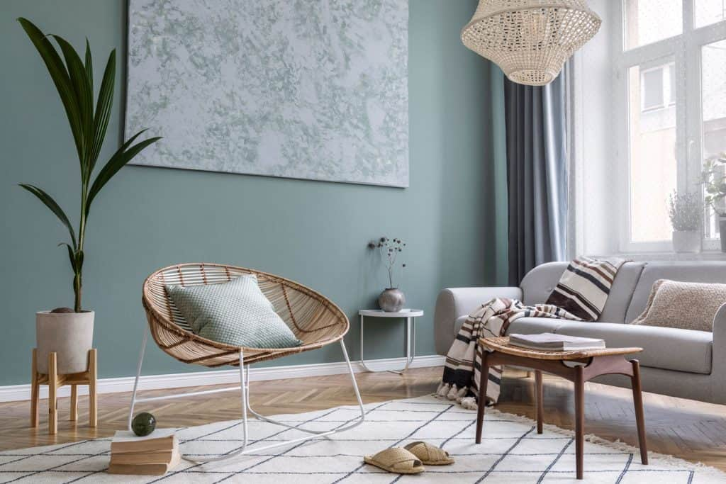 A contemporary inspired living room with retro styled furnitures and light green colored wall