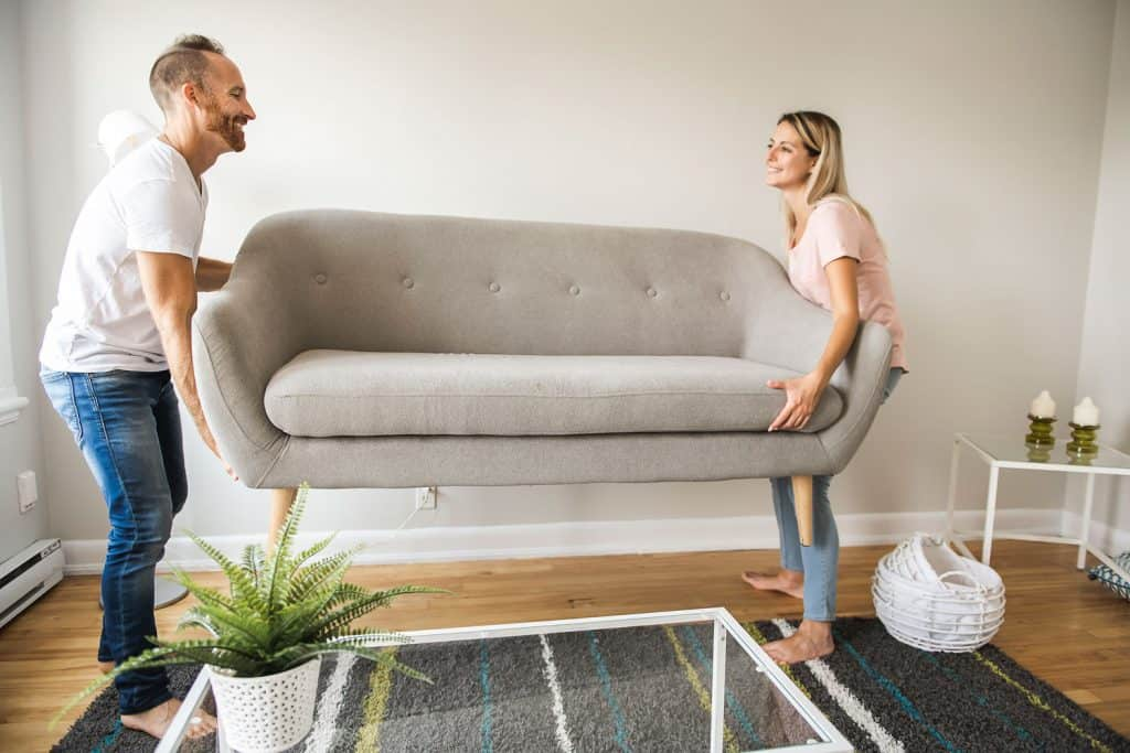 A couple lifting a light gray colored couch and placing it on their living room